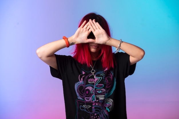 Młoda dziewczyna z różowymi włosami skrzyżowanymi rękami na twarzy.