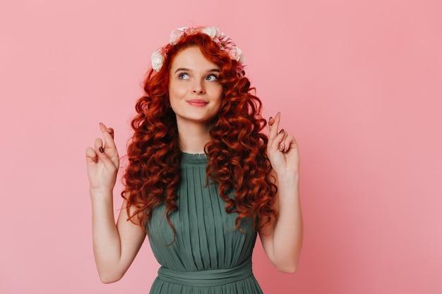 Młoda dziewczyna z rudymi włosami i kwiatami na głowie krzyżuje palce. portret kobiety o niebieskich oczach w zielonej sukience na różowej przestrzeni.