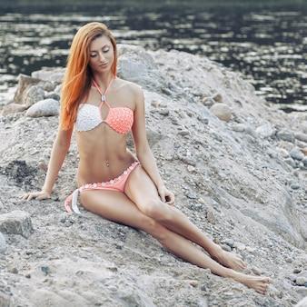 Młoda dziewczyna z rudymi włosami w bikini na plaży