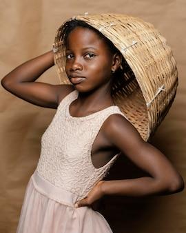 Młoda dziewczyna z słomianym koszem na głowie