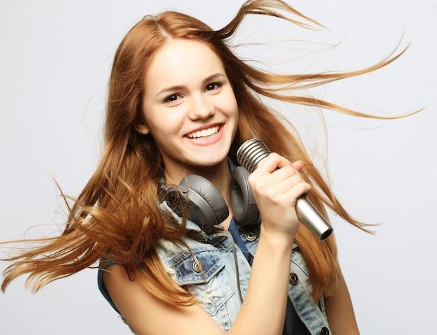 Młoda dziewczyna z śpiewem mikrofonu