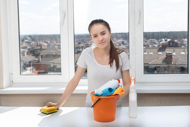 Młoda dziewczyna z środków czyszczących do łazienki, umywalki, toalety, gąbki i szmat