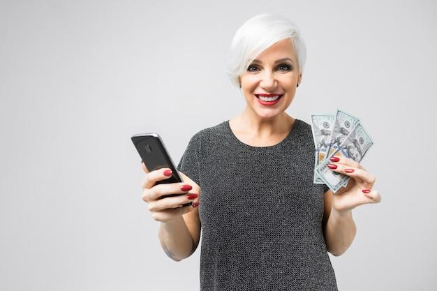 Młoda dziewczyna z telefonem i fanem dolarów w jej rękach stoi na świetle