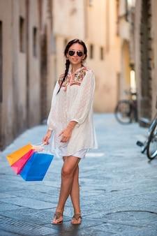 Młoda dziewczyna z torba na zakupy na wąskiej ulicie w europa. portret pięknej kobiety szczęśliwy gospodarstwa torby na zakupy uśmiechnięty