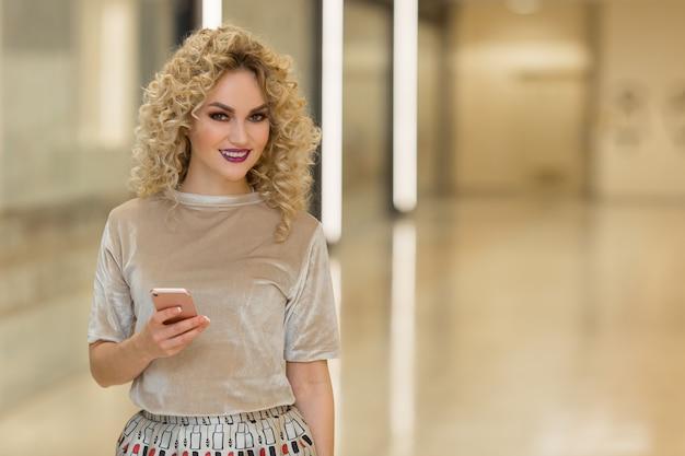 Młoda dziewczyna z torbami rozmawia przez telefon komórkowy w centrum handlowym