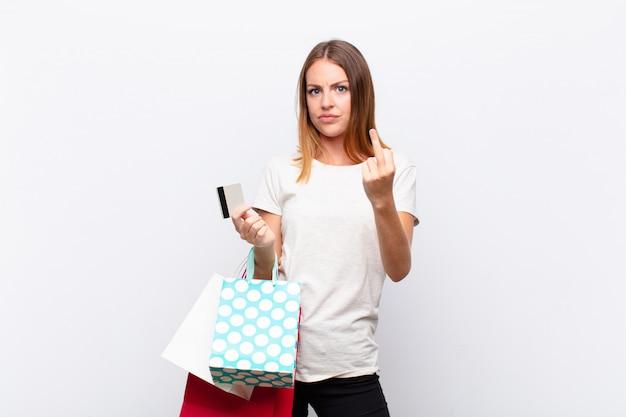 Młoda dziewczyna z torby na zakupy i karty kredytowej czuje się zły, odwracając środkowy palec