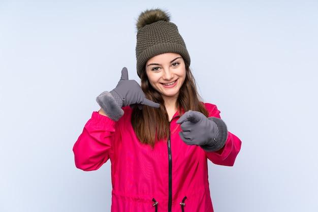 Młoda dziewczyna z zimowym kapeluszem odizolowywającym na niebiesko robi telefonowi gest i wskazuje przód