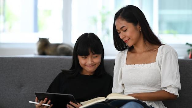 Młoda dziewczyna za pomocą cyfrowego tabletu odrabia lekcje online podczas zajęć dodatkowych ze swoim korepetytorem.