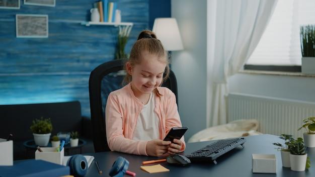 Młoda dziewczyna za pomocą smartfona z ekranem dotykowym przy biurku