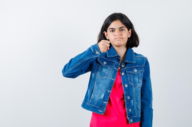 Młoda dziewczyna zaciskając pięść w czerwony t-shirt i dżinsową kurtkę i patrząc poważnie. przedni widok.