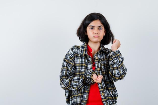 Młoda dziewczyna zaciskając pięści w kraciastej koszuli i czerwonej koszulce i patrząc poważnie, widok z przodu.