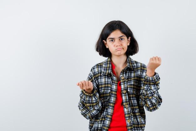 Młoda dziewczyna zaciskając pięści w kraciastej koszuli i czerwonej koszulce i wygląda ładnie. przedni widok.