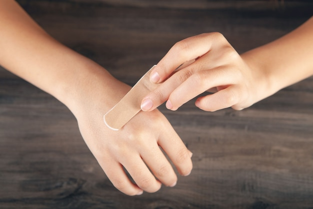 Młoda dziewczyna zakłada bandaż na ramię