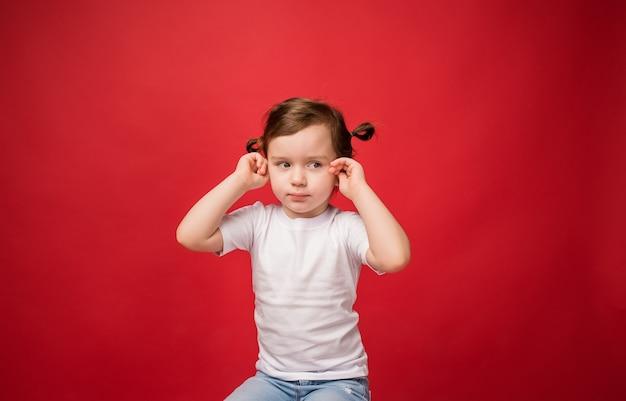 Młoda dziewczyna zakryła uszy palcami