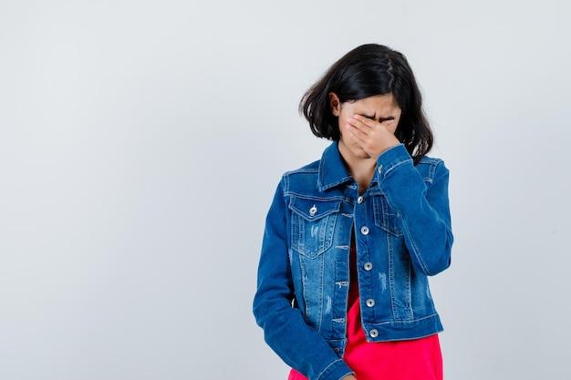 Młoda dziewczyna zakrywa oczy ręką w czerwonej koszulce i dżinsowej kurtce i wygląda na zmęczoną