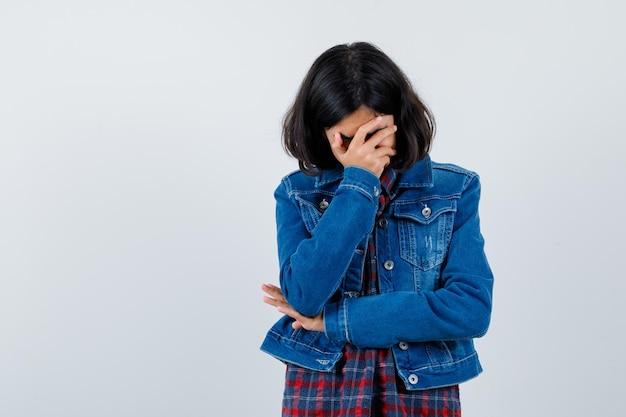 Młoda dziewczyna zakrywa twarz, trzymając rękę na łokciu w kraciastej koszuli i dżinsowej kurtce i wygląda na zmęczoną.