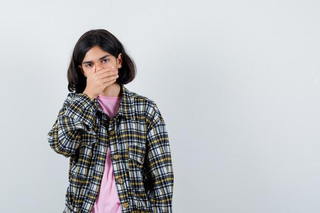 Młoda dziewczyna zakrywa usta ręką w kraciastą koszulę i różową koszulkę i wygląda nieśmiało. przedni widok.