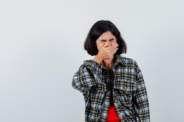 Młoda dziewczyna zakrywa usta ręką w kraciastej koszuli i czerwonej koszulce i wygląda na wyczerpaną. przedni widok.
