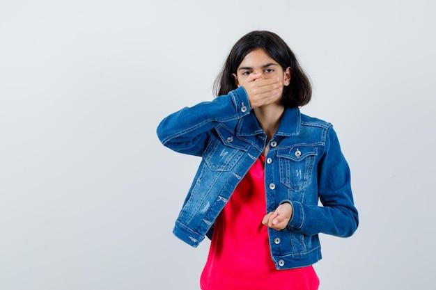 Młoda dziewczyna zakrywa usta ręką, zaciskając pięść w czerwonej koszulce i dżinsowej kurtce i patrząc nieśmiało, widok z przodu.