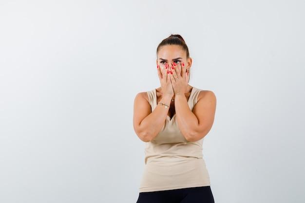 Młoda dziewczyna zakrywająca usta i nos rękami w beżowej górze, czarne spodnie i patrząc podekscytowany, widok z przodu.