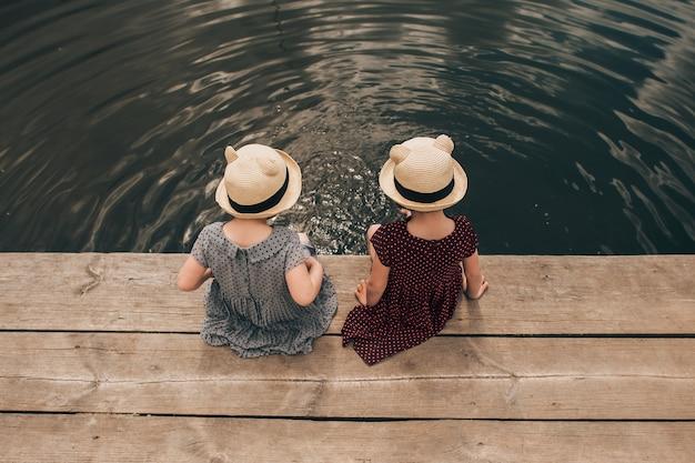 Młoda dziewczyna zanurzenie nóg w jeziorze od krawędzi drewnianych stacji dokującej łodzi
