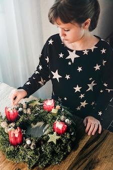 Młoda dziewczyna zapala ostatnią czwartą świecę na wieńcu adwentowym przed bożym narodzeniem szwajcarska tradycja