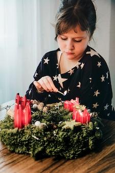 Młoda dziewczyna zapala ostatnią czwartą świeczkę w wieńcu adwentowym na tydzień przed bożym narodzeniem w szwajcarii
