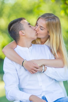 Młoda dziewczyna zaskakuje swojego chłopaka uściskiem od tyłu i pocałunkiem w usta na randce na łonie natury.