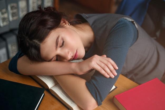 Młoda dziewczyna zasnęła podczas czytania książki.