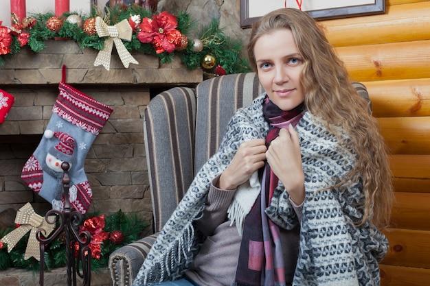 Młoda dziewczyna zawinięta w kratę siedzi na krześle, świąteczne dekoracje