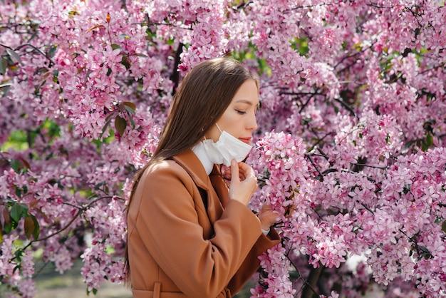Młoda dziewczyna zdejmuje maskę i oddycha głęboko po zakończeniu pandemii w słoneczny wiosenny dzień