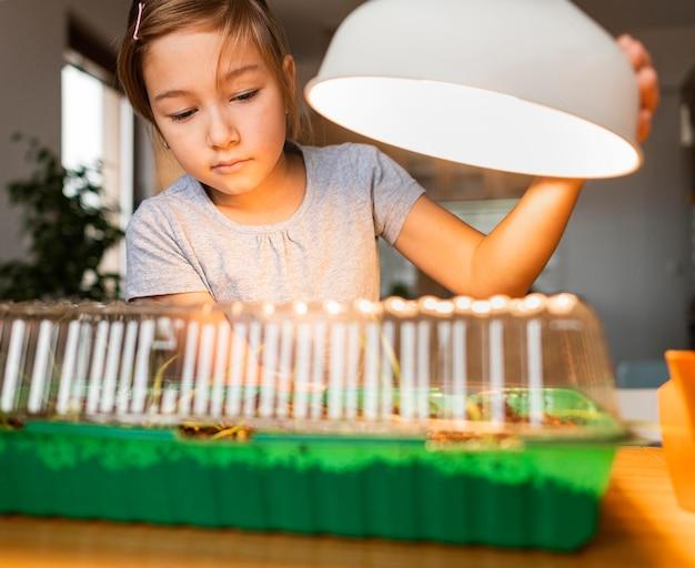 Młoda dziewczyna ze światłem do uprawy roślin