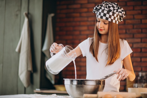 Młoda dziewczynka pieczenia ciasta w kuchni na śniadanie