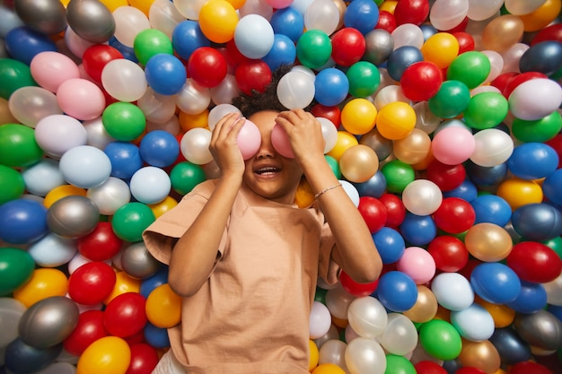 Młoda dziewczynka, zabawy z piłkami w basenie w parku rozrywki
