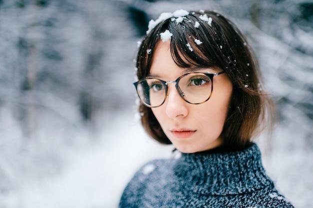 Młoda dziwna piękna urocza urocza dziewczyna w portret swetra z dzianiny na zewnątrz w lesie zimą. modny model w modnych okularach z zamarzniętym śniegiem hukiem włosów. ładna twarz kobiety