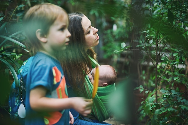 Młoda dżungla z dzieckiem na temblaku i małym chłopcem