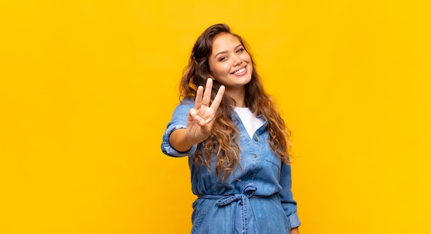 Młoda ekspresyjna kobieta pozuje na żółtej ścianie
