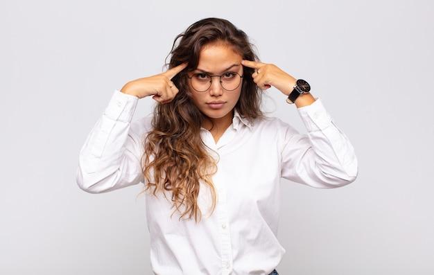 Młoda ekspresyjna kobieta w okularach i elegancka biała bluzka pozuje na białej ścianie