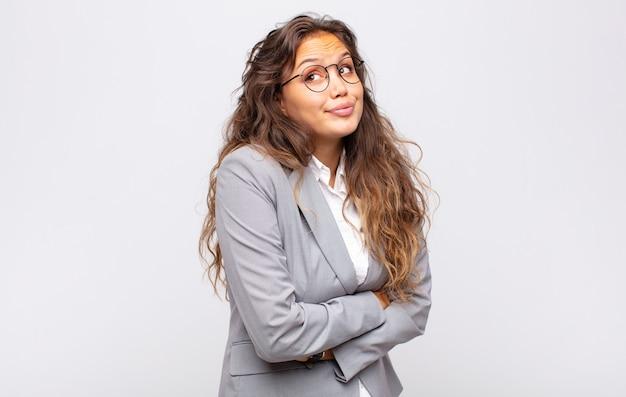 Młoda ekspresyjna kobieta w okularach i eleganckim garniturze pozuje na białej ścianie