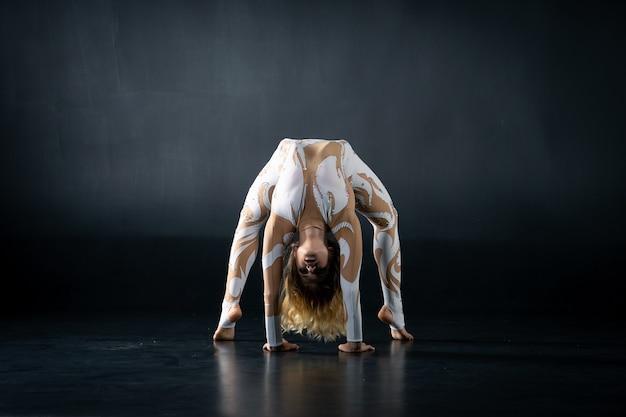 Młoda elastyczna dziewczyna wykonuje akrobatyczne elementy na podłodze