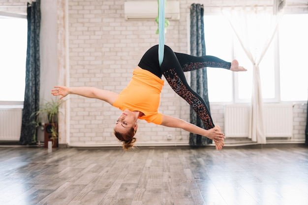Młoda elastyczna zdrowa kobieta robi powietrzny joga w gym