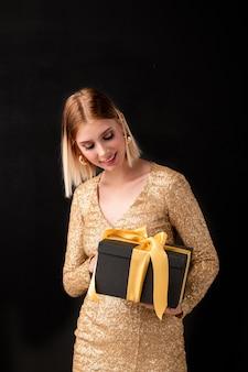 Młoda elegancka blond kobieta w złotej sukience imprezowej, patrząc na czarne pudełko z żółtym węzłem na górze, zgadując, co jest w środku