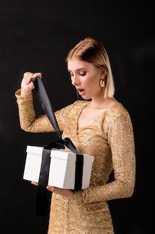 Młoda elegancka dama w błyszczącej sukience rozwiązuje czarną jedwabną wstążkę wiążącą biały gftbox, patrząc w przód na prezent urodzinowy