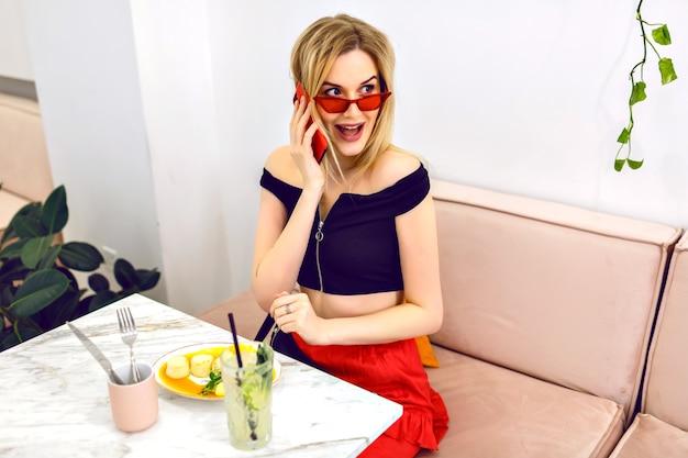 Młoda elegancka dziewczyna pozuje w miejskiej nowoczesnej kawiarni, rozmawia z chłopakiem dowcip przez telefon i delektuje się śniadaniem, szczęśliwe emocje podekscytowane.