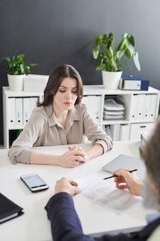 Młoda elegancka kandydatka siedząca przy biurku przed pracodawcą podczas rozmowy kwalifikacyjnej, zadając pytania na temat swojego poprzedniego miejsca pracy