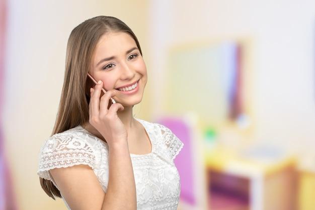 Młoda elegancka kobieta opowiada na telefonie komórkowym