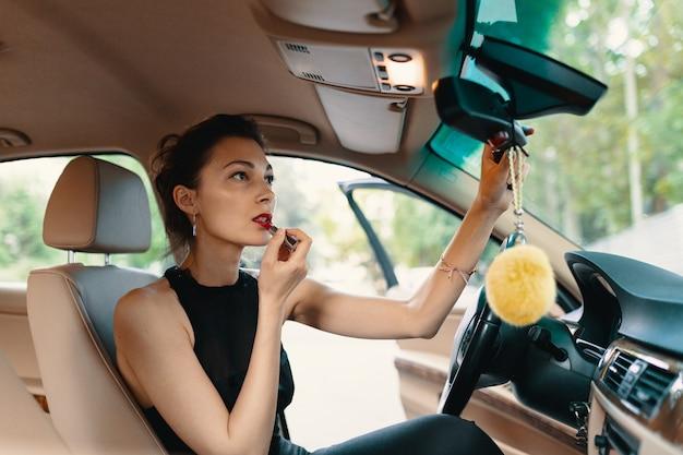 Młoda elegancka kobieta patrzeje w samochodowym lusterku podczas gdy applin