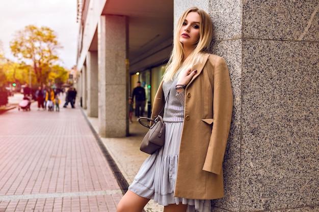 Młoda elegancka kobieta pozuje na ulicy w pobliżu centrum handlowego, modne stroje glamour, beżowy płaszcz, srebrny sweter i sukienka, wiosna, naturalne piękno