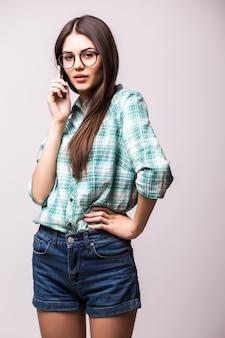 Młoda elegancka kobieta rozmawia z telefonu komórkowego przed białym