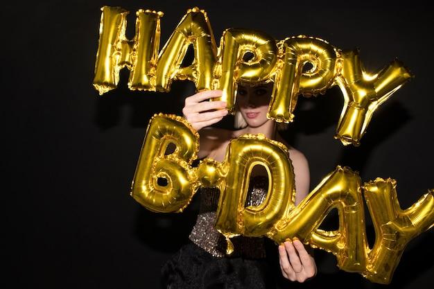 Młoda elegancka kobieta trzyma balony w kształcie litery złotego koloru, gratulując ci urodzin na czarnym tle